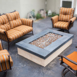 The patio area surrounding the fire pit is dark stained stamped concrete